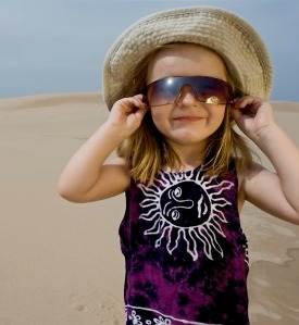 Little, cute girl wearing sunglasses and funny hat.